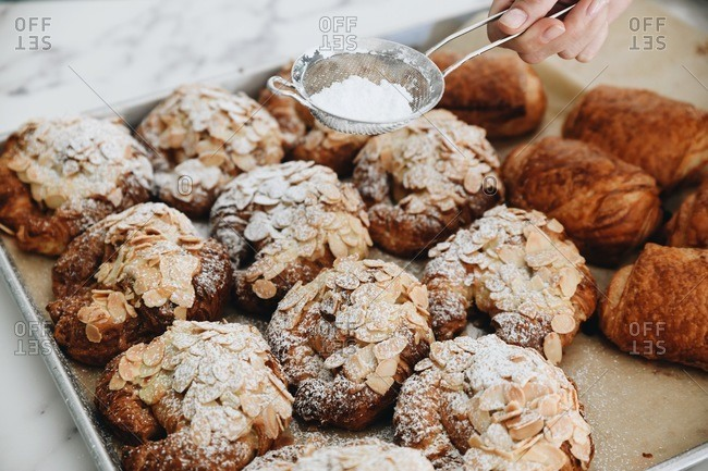 Hand sifting powdered sugar over fresh baked almond pastries on a baking tray