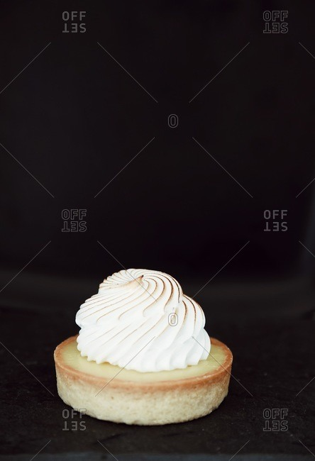A small custard tart with meringue on dark background