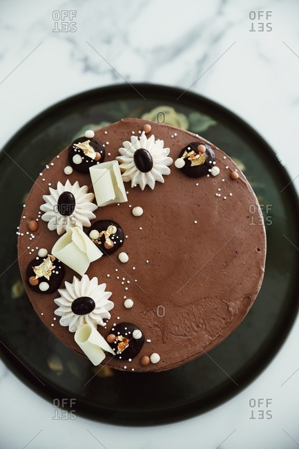 Top view of a chocolate cake topped with candies and gold leaf