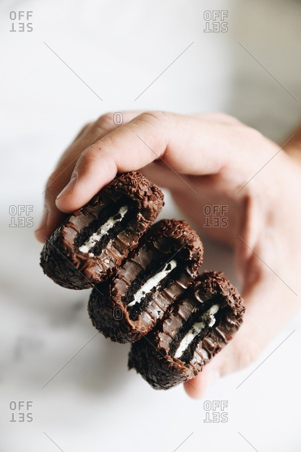 Hand holding chocolate sandwich cookie stuffed fudge cookies
