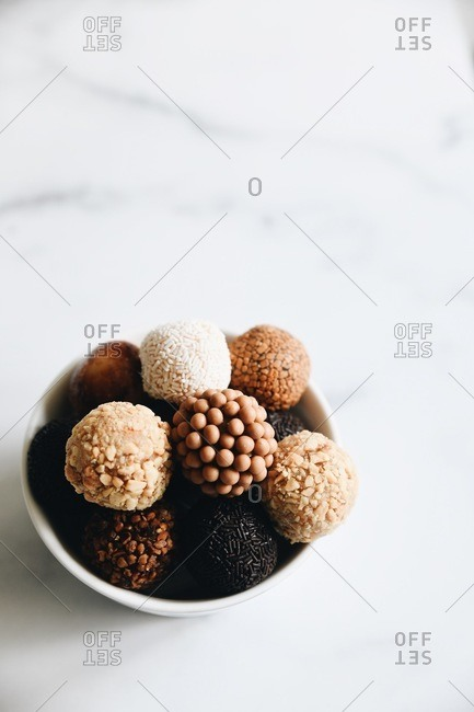 Variety of Brazilian brigadeiros in a dish on marble surface