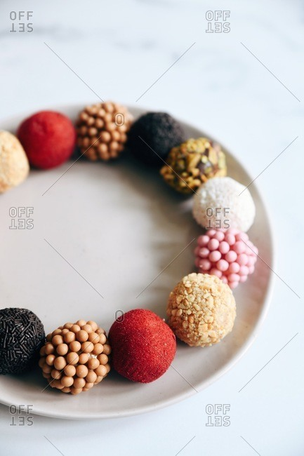 Variety of Brazilian brigadeiros on a plate on marble surface