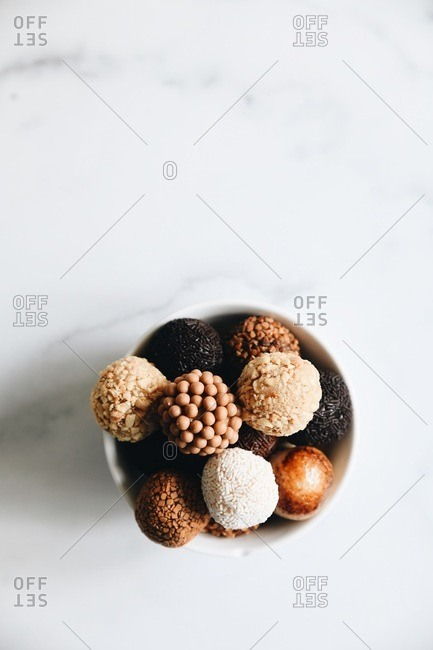 Bowl filled with a variety of Brazilian brigadeiros on marble surface
