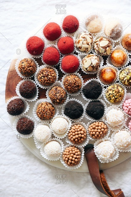 Variety of Brazilian brigadeiros on round board with leather strap