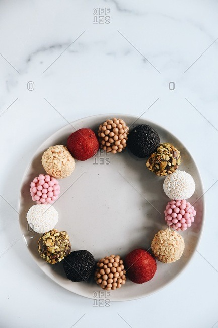 Assorted Brazilian brigadeiros on a round plate on marble surface