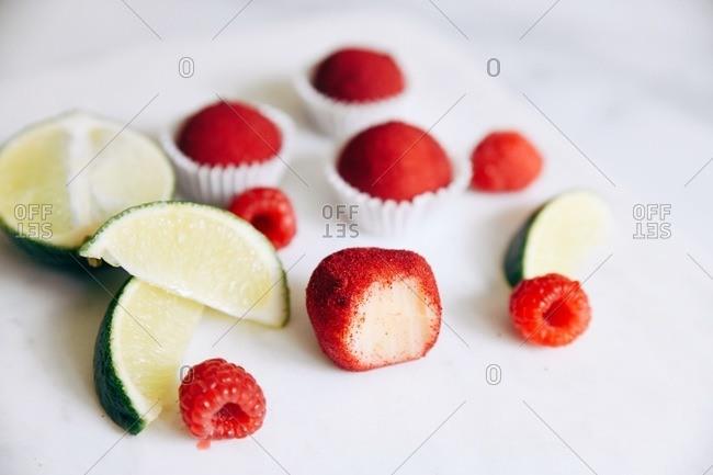 Raspberry lime white chocolate brigadeiro truffles on white surface