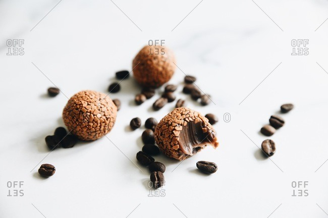 Cappuccino brigadeiros missing a bite on white surface with coffee beans