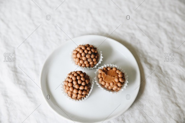 Caramel crunch brigadeiros on a small plate on white background