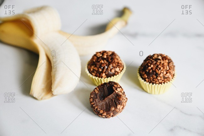 Bananas and nut brigadeiro missing a bite on marble surface
