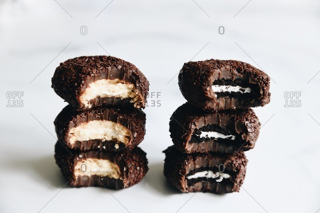 Cookie stuffed fudge cookies stacked on white surface