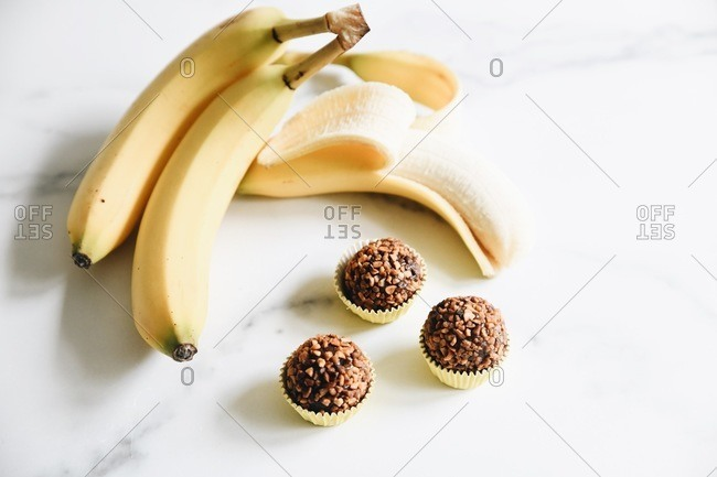 Bananas and nut brigadeiro truffles on a white marble surface