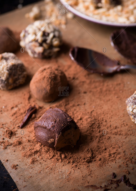 Close up of assorted dark chocolate truffles with cocoa powder, biscuit and chopped hazelnuts on baking paper
