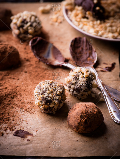 Various dark chocolate truffles with cocoa powder, biscuit and chopped hazelnuts on baking paper