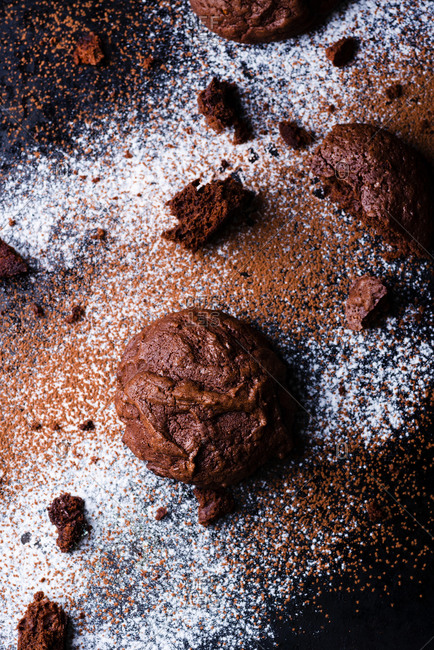 Homemade chocolate cookies on dark background covered in powdered sugar and cocoa