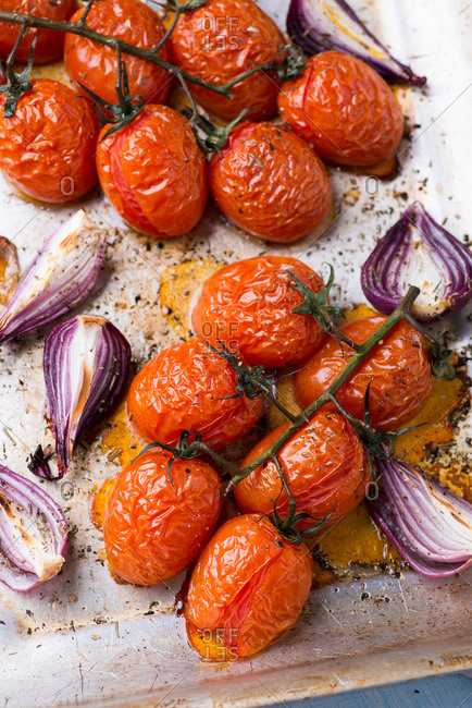 Oven roasted tomatoes and onions on metal baking tray viewed from above
