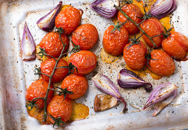 Overhead view of oven roasted tomatoes and onions on metal baking tray