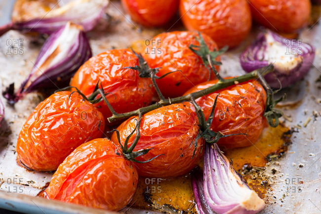 Oven roasted tomatoes and onions on metal baking tray