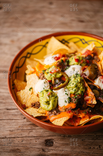 Nachos with guacamole and sour cream in a bowl on wooden surface