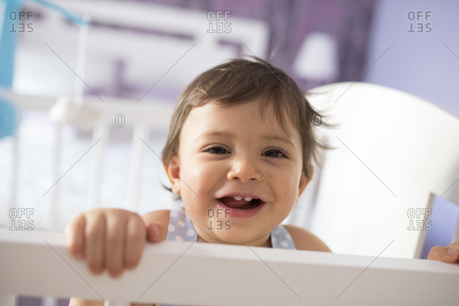 Happy toddler standing up in bedroom crib