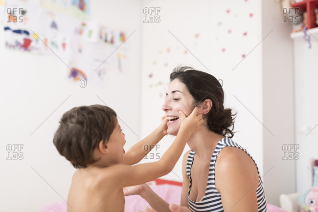 Little boy touching mother's face while playing with his mother in the bedroom