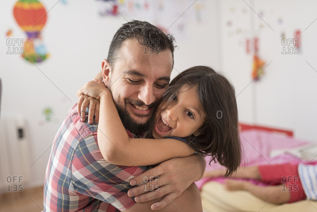 Father embraces his daughter with much love in her bedroom