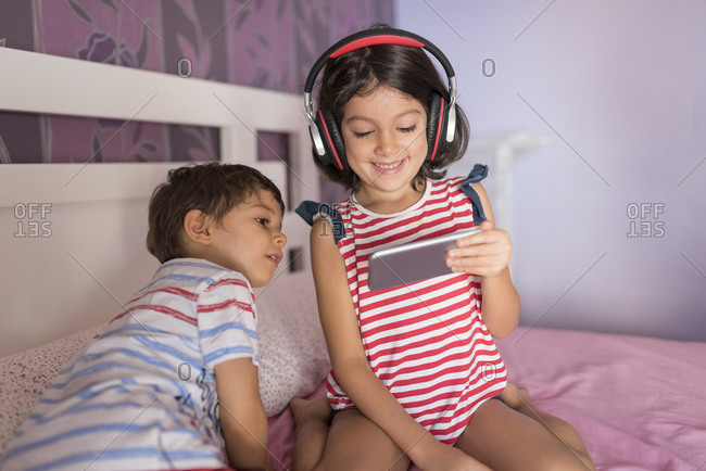 Brother and sister play on their bed with technology and headphones