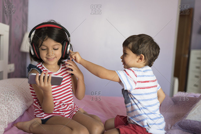 Sister and brother play on their bed with technology and headphones