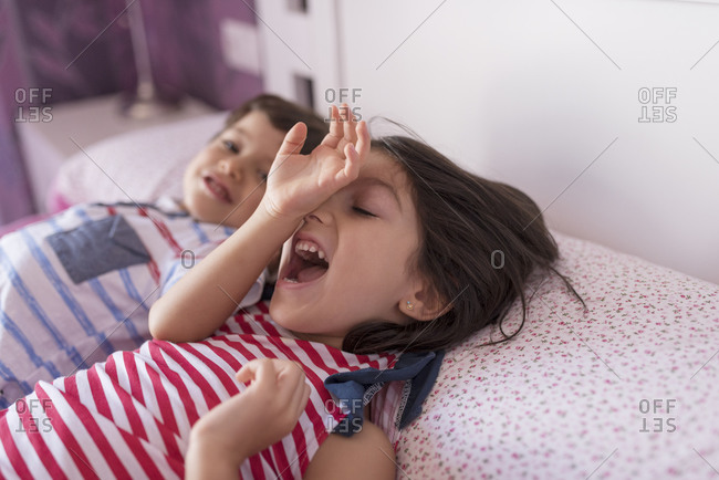 Siblings playing in bed at home on boring summer day