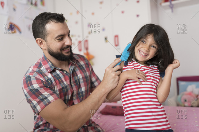 Father combing his daughter's hair in her bedroom