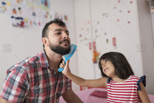 Daughter combs her father's beard while playing