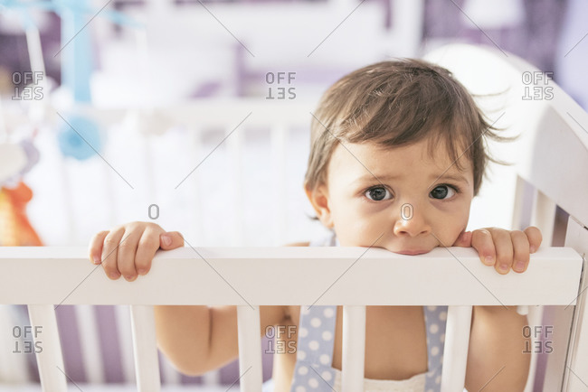 Adorable toddler standing in his bedroom crib biting the rail