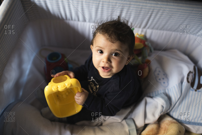 Infant boy sitting in his crib playing with toys and looking at camera