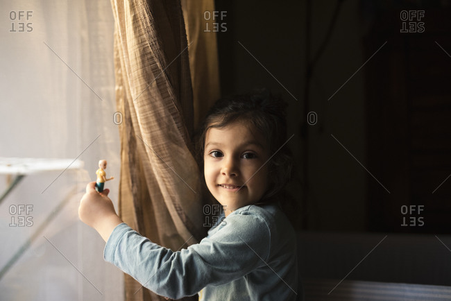 Little girl plays with a doll next to the window in her living room