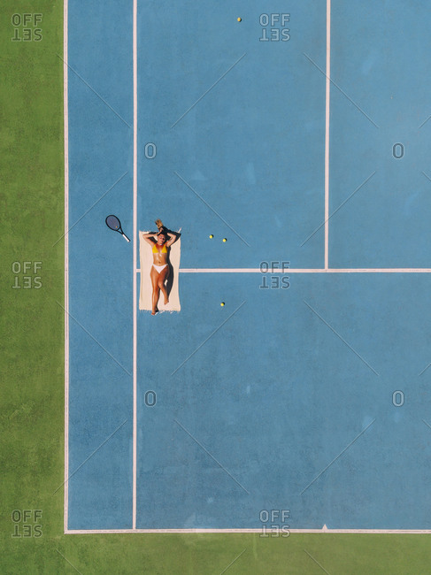 Blond woman lying on a towel on a tennis court with a tennis racket sunbathing