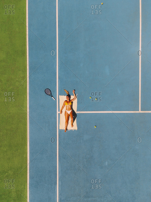 Young blond woman lying on a towel on a tennis court with a tennis racket sunbathing