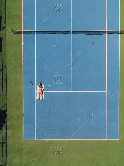 Aerial view of a blond woman sunbathing on a green and blue tennis court with a tennis racket