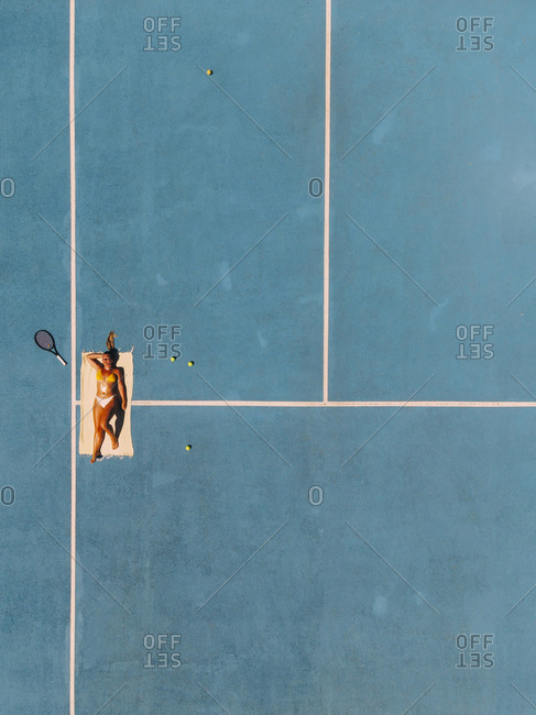 Young blond girl lying on a blue tennis court with a tennis racket sunbathing