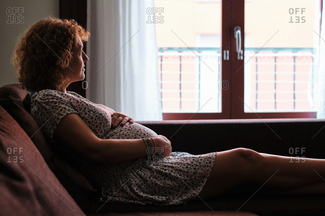 Adult pregnant woman in her late thirties touching her belly and looking out window