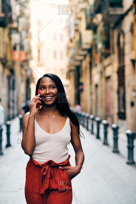 Young black woman walking on the streets using a cell phone