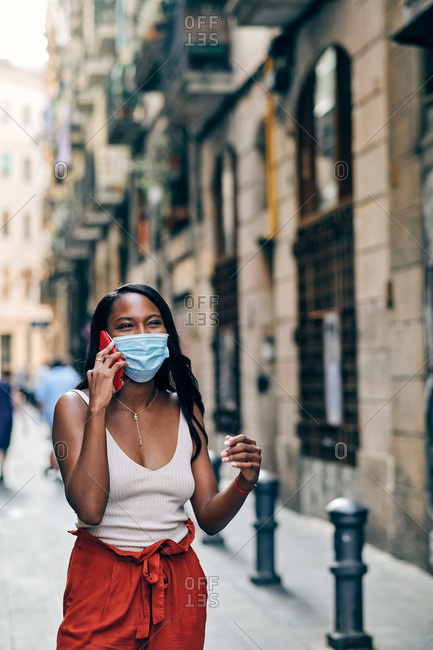 Black woman with face mask using mobile on the street wearing a facemask