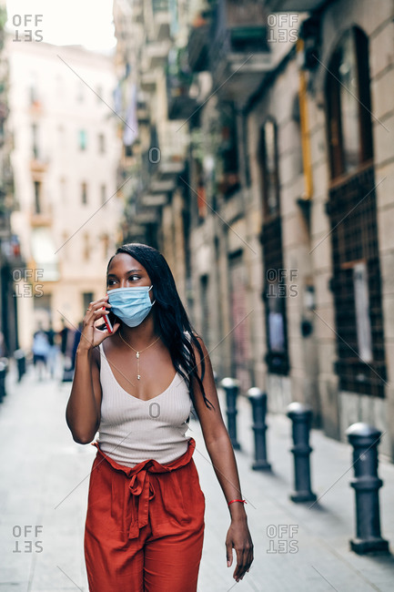Young black woman with face mask using mobile on the street wearing a facemask