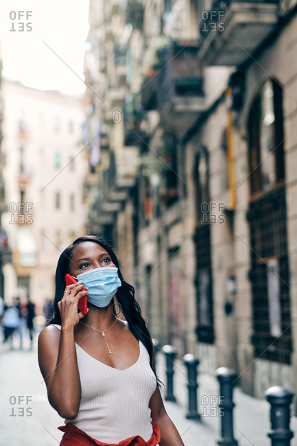 Young black woman with face mask using mobile on the street during the coronavirus outbreak