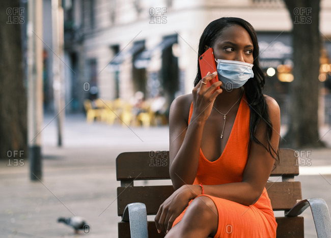 Stylish young black woman using mobile on the street during the coronavirus outbreak
