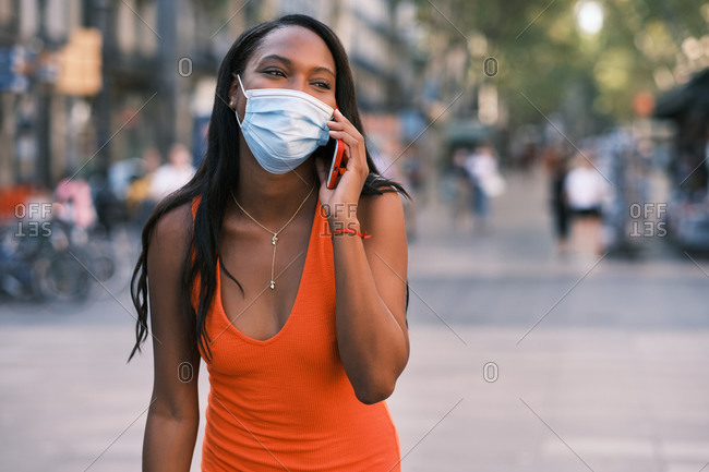 Happy black woman with face mask using mobile on the street wearing a facemask