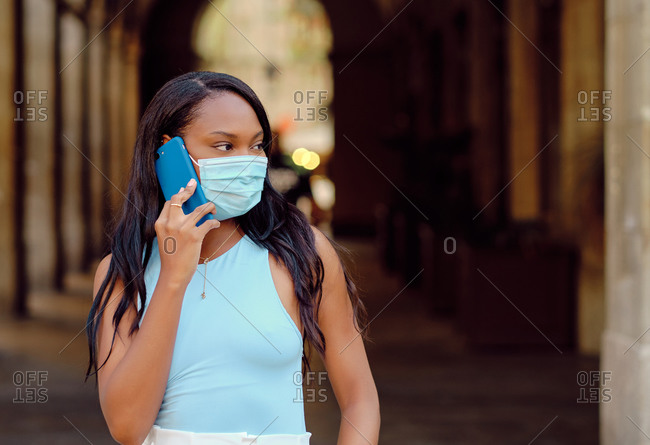 Young black woman wearing a light blue shirt and mask using smartphone