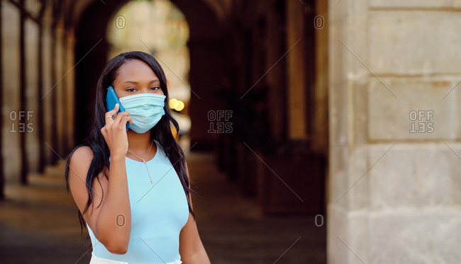 Young black woman wearing a light blue shirt and mask using smartphone and looking at camera