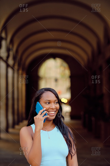 Young black woman wearing a light blue outfit and using mobile phone outdoors
