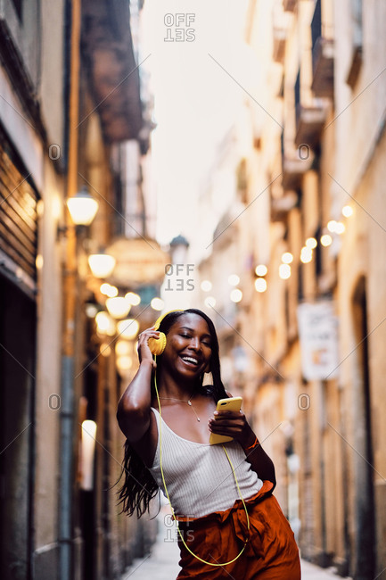 Young afro American woman dancing in the streets with headphones in Barcelona