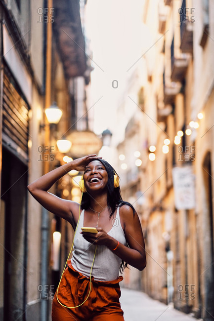 Young afro American woman dancing in the streets with yellow headphones in Barcelona