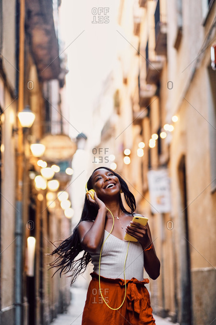 Afro American woman dancing in the streets with yellow headphones in Barcelona